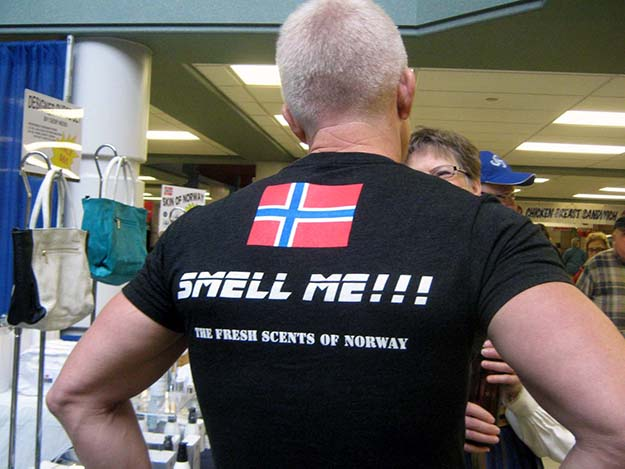 """Photo: Barbara K. Rostad Geir Ness appeals to the sense of smell with two Norwegian perfumes based on """"the fresh scents of Norway."""" Ness chats with a customer while wearing his unique t-shirt marketing tool."""