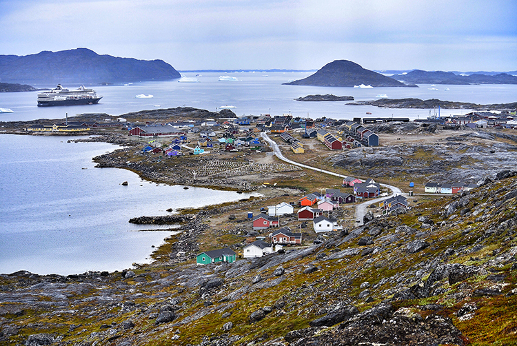 Photo: Elisabeth Beyer Nanortalik is a hardscrabble town, as seen from partway up Ravnefjeldet. Icebergs drift by in the fjord past the colorful houses. Who lives here? The town on a Sunday morning is empty, intriguing.