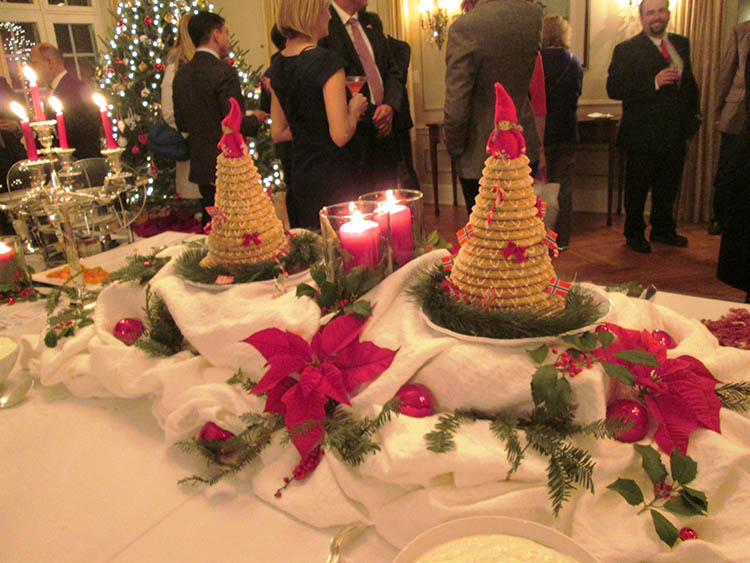 two kransekaker topped with nisser on a decorated table for the Ambassador's Christmas party