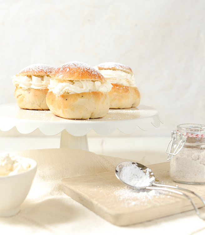 Three fastelavnsboller, cardamom buns stuffed with whipped cream