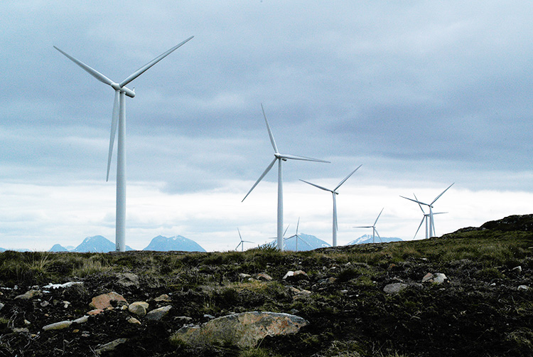 Wind turbines in western Norway with mountain peaks in the background.