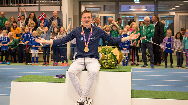 Karsten Warholm sits on the first place podium and shows off his gold medal.