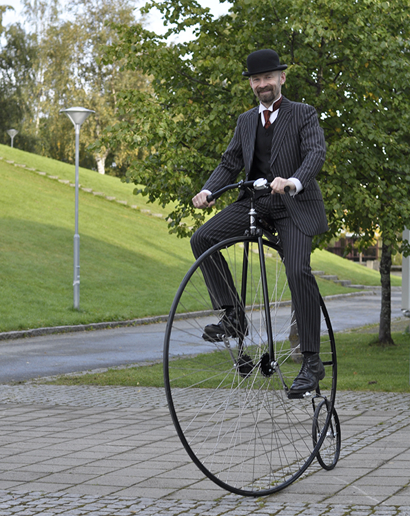 Man on a high-wheeler velocipede.