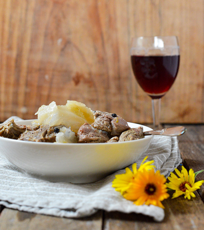 A bowl of fårikål alongside a glass of wine.