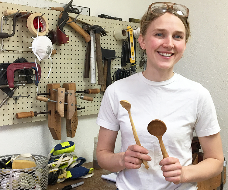 Hirsch holding two spoons and standing in front of woodworking tools.