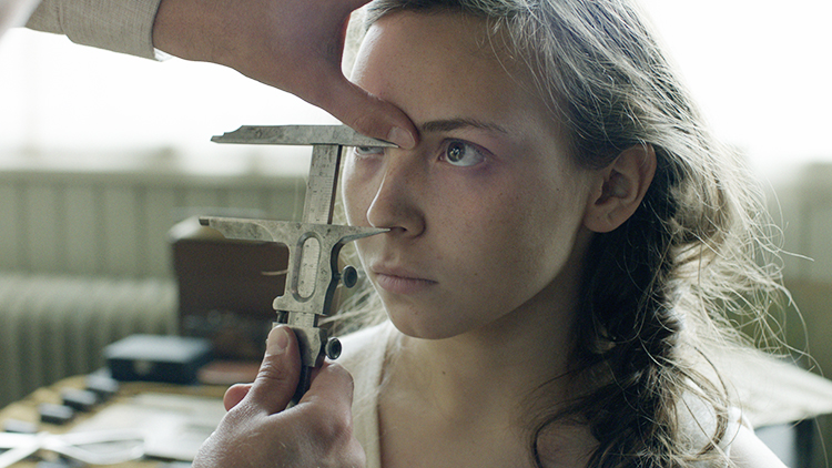 Someone measuring Elle-Marja's facial features.