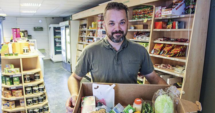 Man holding box of food in vegan store.