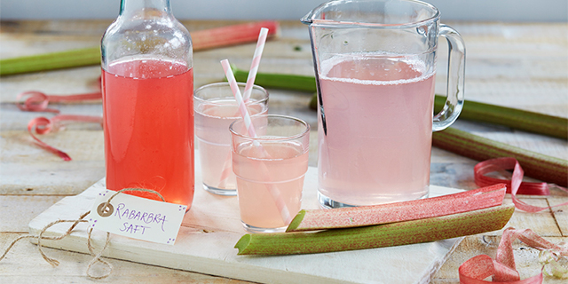 a pitcher and two glasses of pink rabarbrasaft (rhubarb cordial)