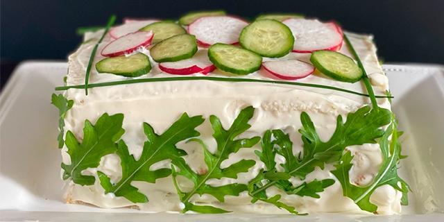 a vegetarian Smörgåsårta (sandwich cake) covered in mayonnaise, arugula leaves, radishes, and cucumbers.