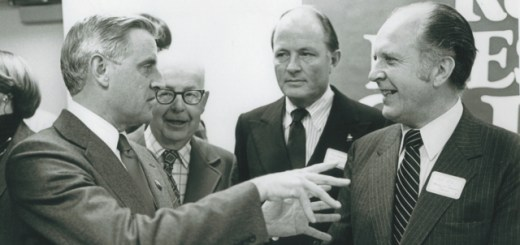 Walter Mondale speaks with three other men in suits