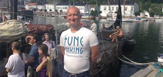 a man in a Tune Viking shirt by a Viking era ship