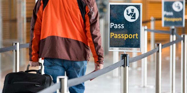 a man walking towards passport control at an airport