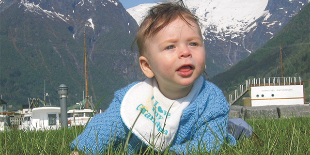 a baby laying on grass with mountains in the background