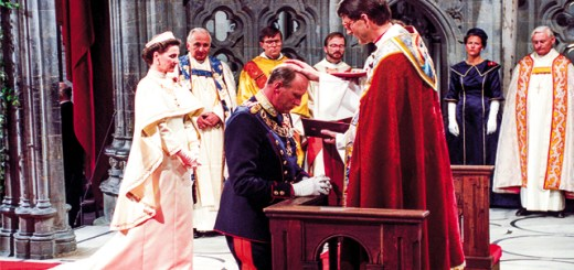 King Harald's consecration at Nidaros Cathedral. King Harald kneels with a bishop placing a hand on his had. Queen Sonja stands in the background.