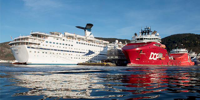 a cruise ship and supply boat in Bergen harbor