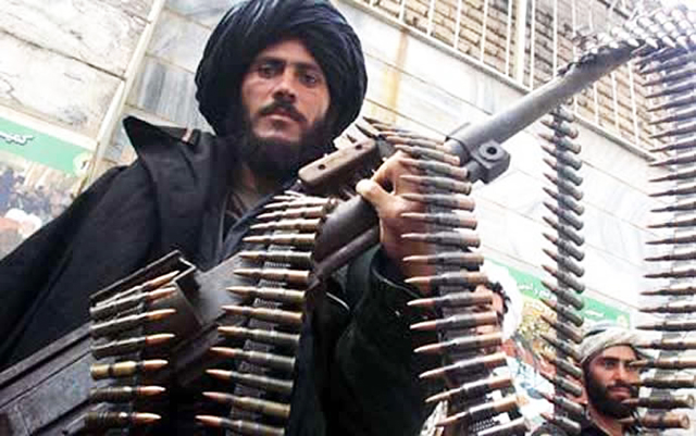 Taliban fighter holding a large gun with rounds of ammunition