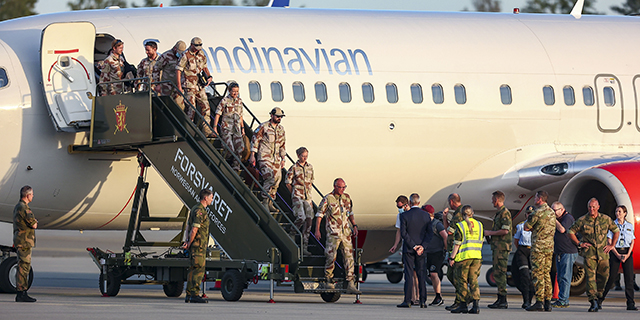 Norwegian soldiers combing off an airplane