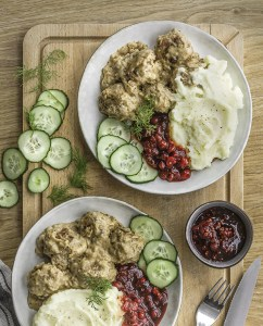 two plates of Swedish meatballs, mashed potatoes, lingonberries, and cucumbers