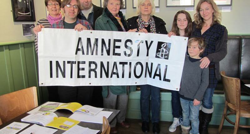 amnesty norwich members with banner at write for rights event
