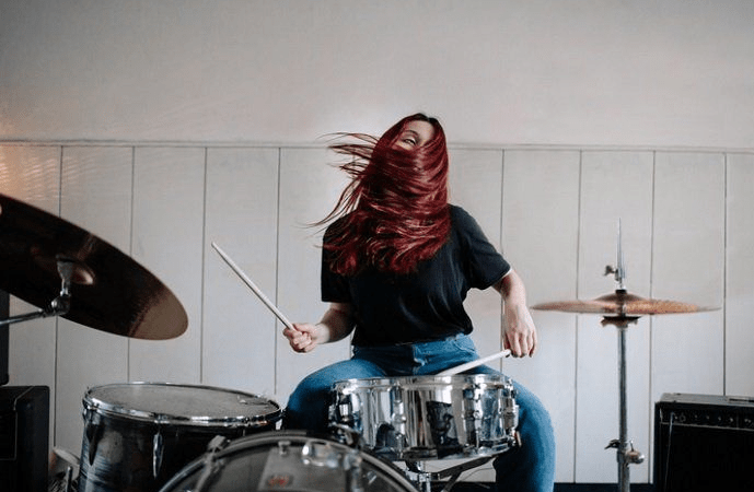 red haired woman playing drums at home