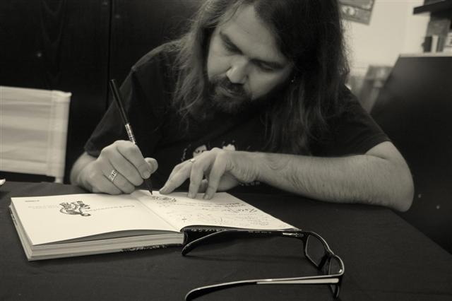 Borja Crespo firmando un ejemplar. Las gafas serán de lejos (especula el entrevistador).