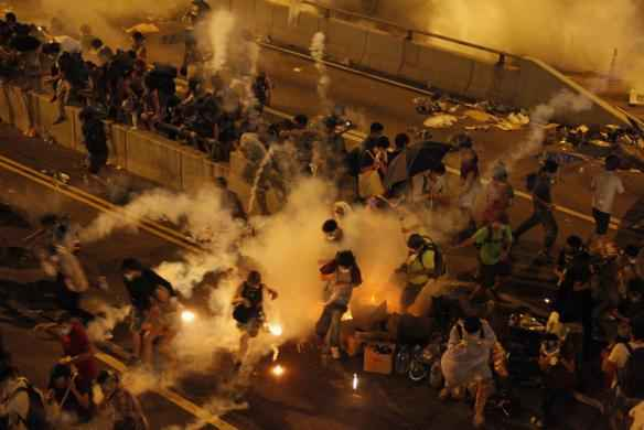 Riot police fire teargas to disperse protesters after thousands of demonstrators blocked the main street to the financial Central district outside the government headquarters in Hong Kong