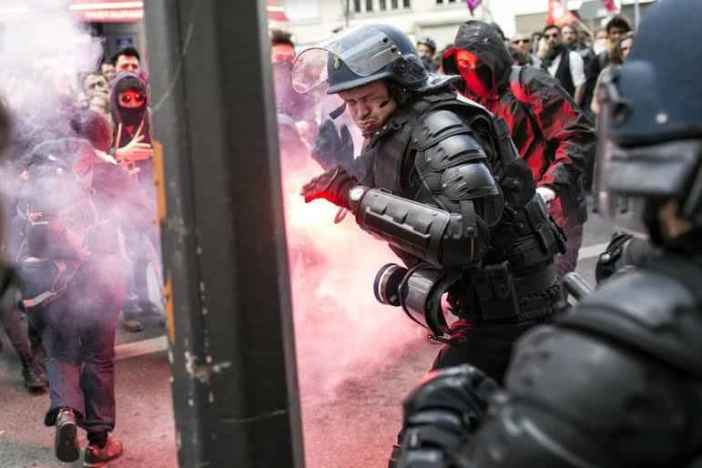 A policeman reacts during a clash with protestors during a protest against the proposed changes to France's working week and layoff practices, in Lyon, central France, Thursday, April 28, 2016. French protesters are back on the streets over proposed reforms to the country's labor rules and strikers have forced cancellations and delays at two airports serving Paris. (AP Photo/Laurent Cipriani) CIP104 (Laurent Cipriani / The Associated Press)
