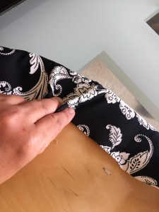 Image of placing a fold and holding it in place onto the curve of the chair pad