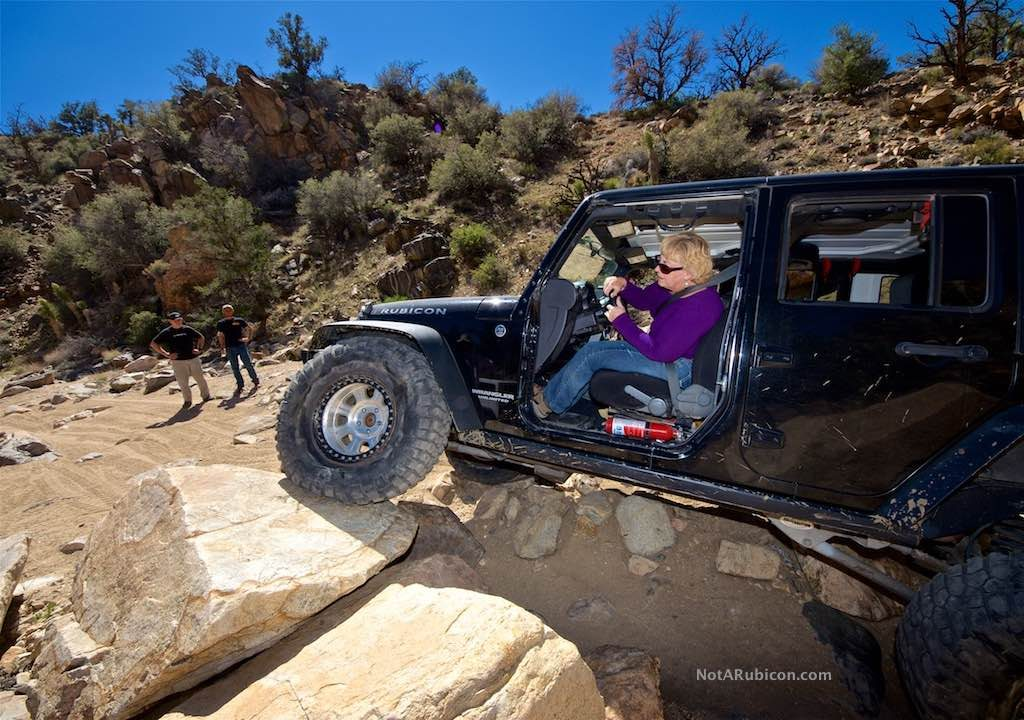 Black Jeep going over large rocks
