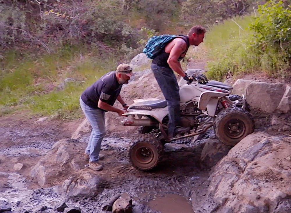 Keven Kelly, co-founder of Combat Crawlers helping a quad-rider up the trail in Los Pinos Peak in the Corral Canyon OHV area of Southern California.