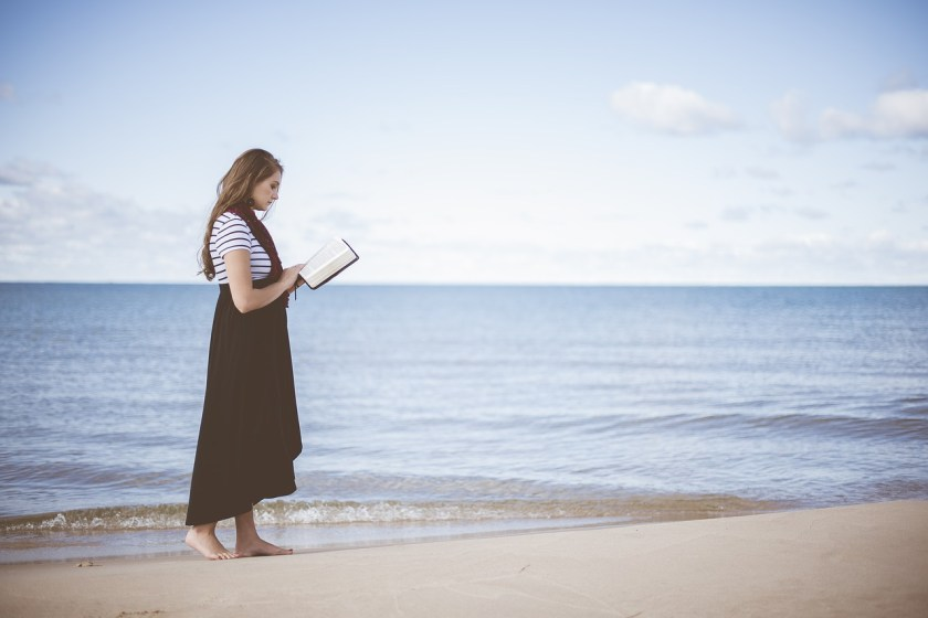 woman reading on beach near ocean