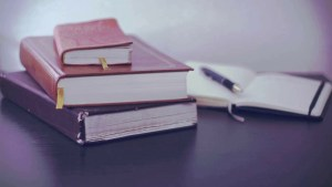 stack of books next to open notebook with pen