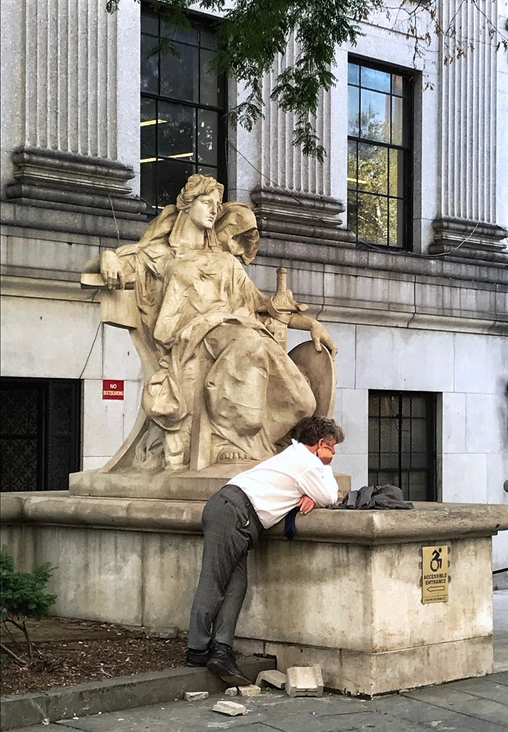 """The statue of """"Justice"""" reclines near the rear entrance of the New York State Supreme Court Building. Photo by Rick Stachura. August 15, 2019."""