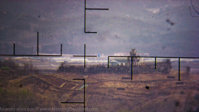 From atop a hill on the North Korean side of the DMZ, you could spy on Joint South Korean / USA / UN military instalations in South Korea by using creepy powerful binoculars with cross-hairs.