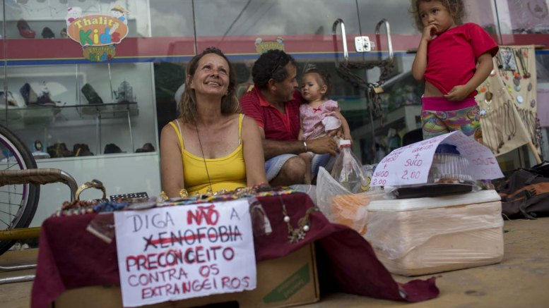 """Una mujer brasileña vende artesanía con un letrero que dice """"Di no a la xenofobia: prejuicio contra los extranjeros"""" en una feria callejera en la ciudad de Boa Vista, Roraima, Brasil, el 25 de febrero de 2018./ AFP PHOTO / Mauro PIMENTEL"""