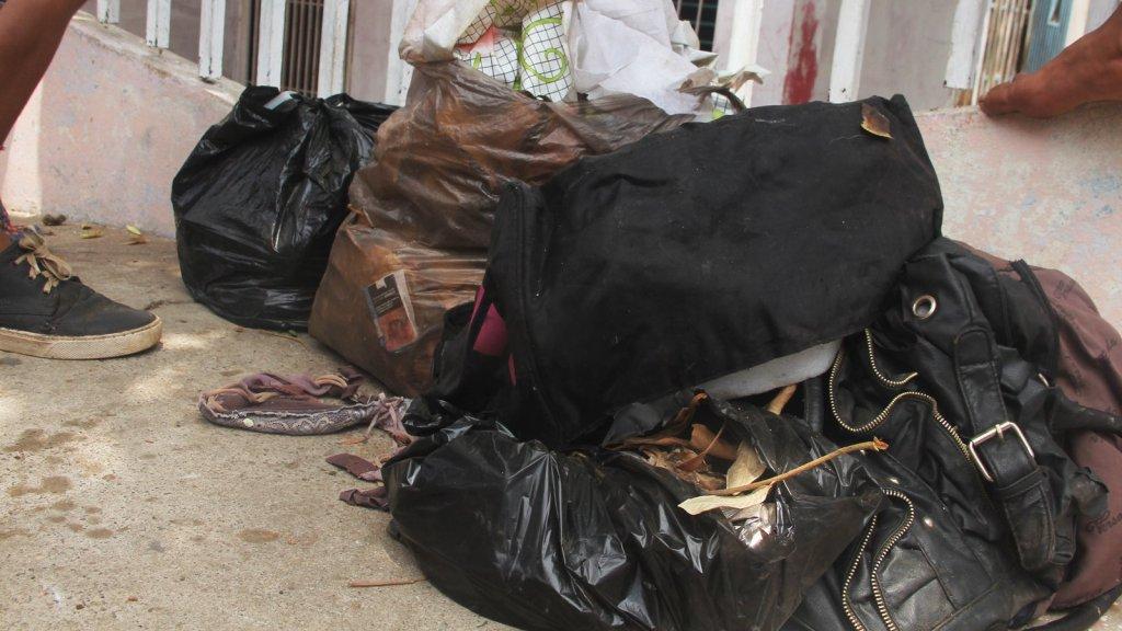 Frente a la casa donde localizaron a la joven muerta, permanecían varias bolsas de basura, en la que se visualizaba un brassier, una cartera de mujer y bolso viajero.