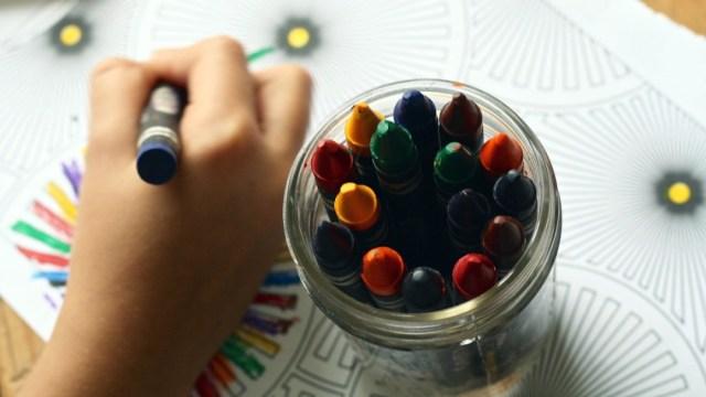 niño escribiendo crayones escuela