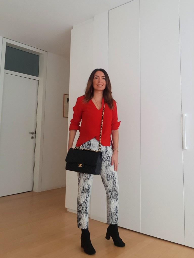 Outfit pitonato con un tocco di rosso vivace