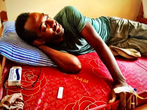 Man with malaria test and IV on a mattress in a pharmacy in rural Uganda