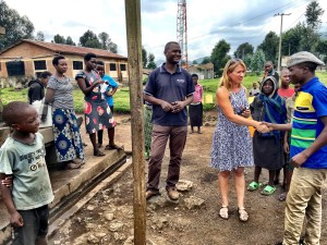 White American woman being interviewed by people in Uganga around town's water source