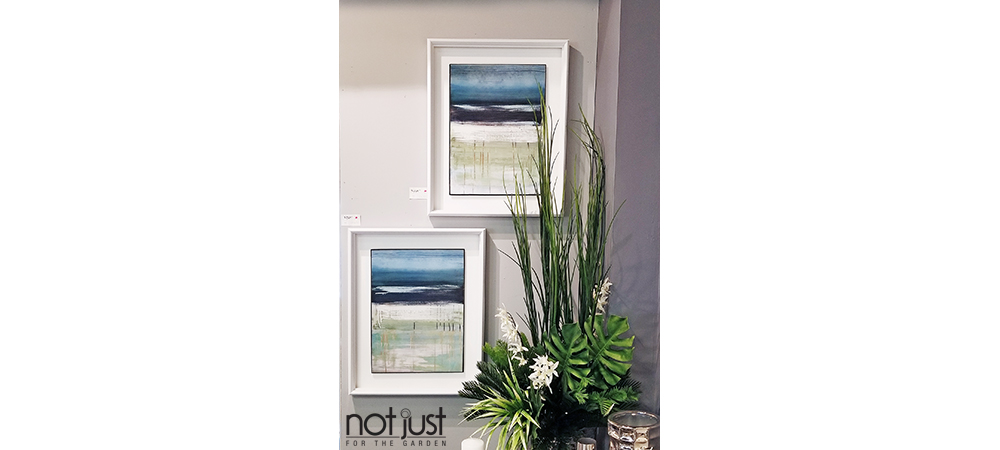 Two White framed abstract ocean horizon paintings in blue, green and white mounted on a wall next to a decorative planter