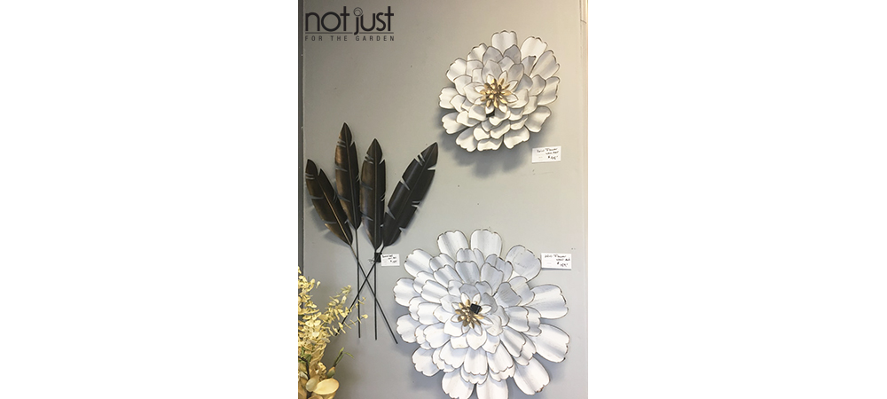 Two white metal flowers mounted on a wall shaped like gerber daisies