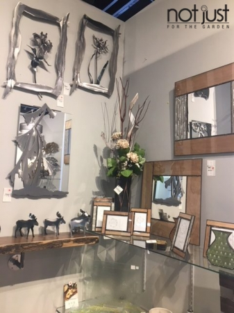 Mirror and photo frames by Canadian artist Bibelot Design, along with mirrors and 3D metal art by Canadian artist Metallic Evolution in the corner of a room in an interior decor setting