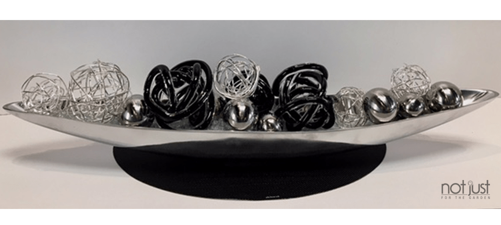 Contemporary table centerpiece of long silver accent piece with metal spheres and black wire balls inside, over a black placemat