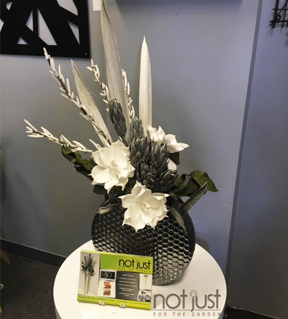 Custom arrangement with white faux flowers and round metal vase on white side table in interior decor setting