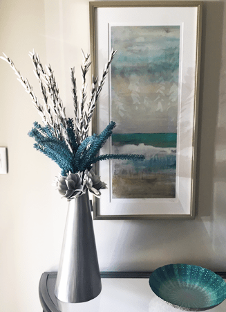 Interior arrangment of faux branches and teal accents in a silver cone chaped vase on a console table against blue beach themed framed painting