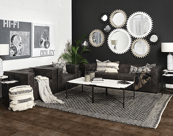 Living room interior design with cog mirrors, dark brown leather couches, coffee table and canvas wall art by Mercana