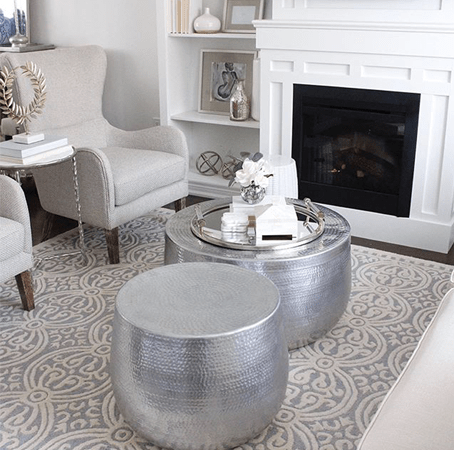 Living room interior design setting with hammered aluminum nordic accent table by Canadian furniture company, Style in Form, over a beige rug with beige upholstered armchairs and white fireplace
