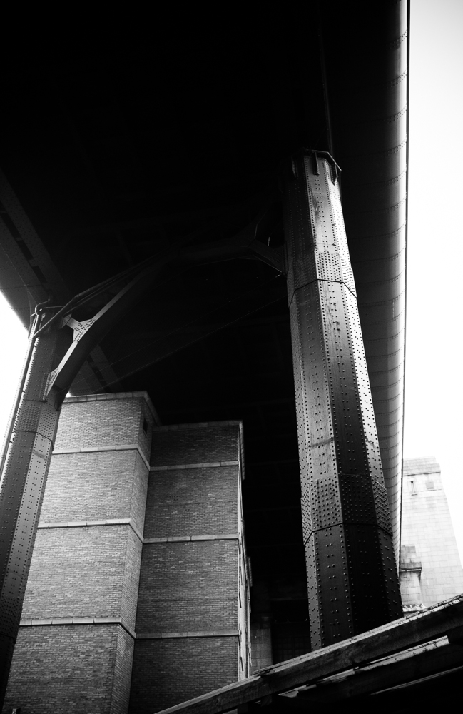 Giant steel support pillars rise skyward from the streets below as the brodge passes over long established buildings.