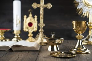 Roman Catholic Church theme. The Cross, Holy Bible, monstrance, rosary and golden chalice on rustic wooden table.